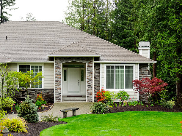 Modern Home Exterior Photograph of a modern home with green grass and trees in front yard. stone house stock pictures, royalty-free photos & images