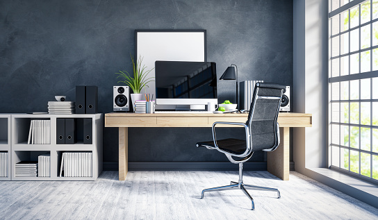 Interior of a modern home office next to a big window. Light wood desk with organized set up of books, office supplies and computer with some room decor around it.