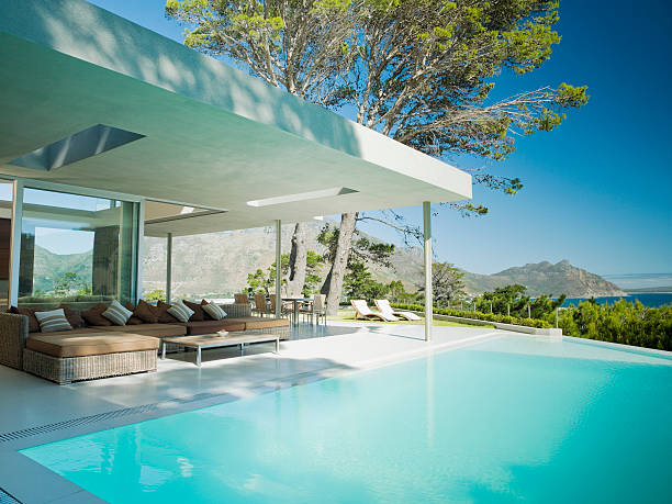 Modern home, patio and infinity swimming pool  infinity pool stock pictures, royalty-free photos & images