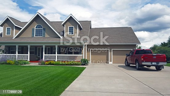 Bigfork,Montana, USA- August 17,2019: Modern Stylish 2 Story home. Front yard with beautiful lawn and red pick-up truck parked in driveway. Two garages.