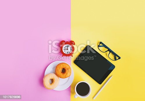istock Modern home workplace, Alarm clock, Cup of coffee, donuts, eyeglasses and tablet on pastel background with copy space 1017625696