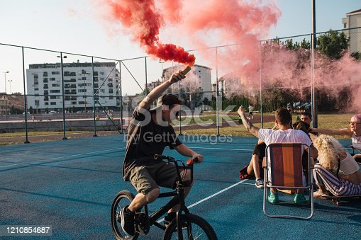 Group of friends playing around with a smoke bomb on a sports court