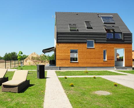 KIEV, UKRAINE - July, 09, 2014:  Modern house construction. Solar water heating (SWH) systems use roof solar panels. Home skylights, dormer, ventilation. Eco smart house energy efficiency.