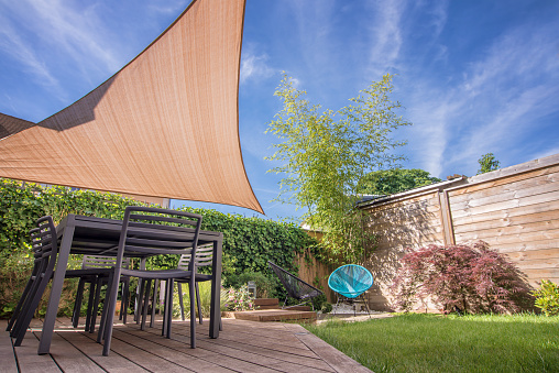 Modern house terrace in summer with table and shade sail