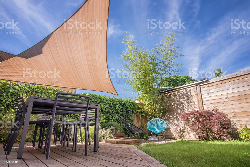 Modern house terrace in summer with table and shade sail stock photo
