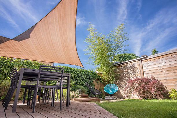 modernes haus im sommer geöffnete terrasse mit tisch und schatten sail - outdoor sonnenschutz stock-fotos und bilder