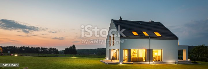 istock Modern house with garden at night 542095422
