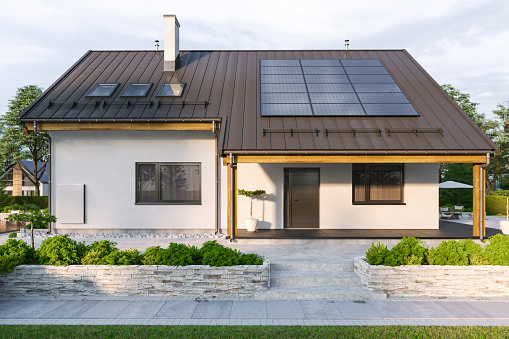 Modern house with solar panels and wall battery for energy storage.