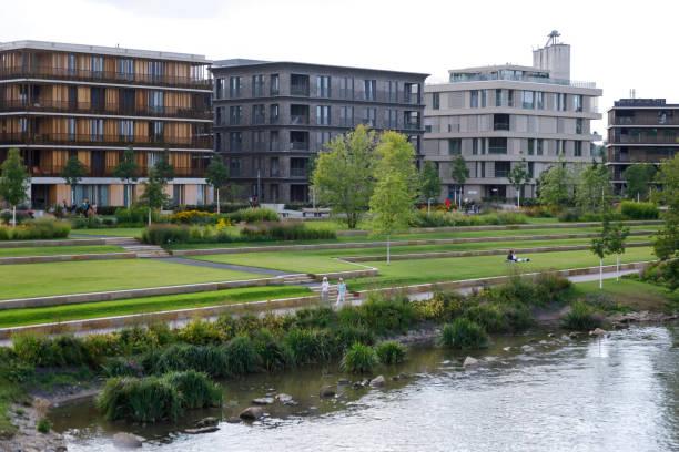 Moderne Häuser während der BUGA Heilbronn Bundesgartenschau 2019. Betonwege zwischen Rasenflächen am Neckarufer. Bild eines gemütlichen Stadtraums. – Foto