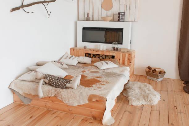 moderne jagd haus schlafzimmer innenraum mit kamin und tierische haut auf bett - jagdthema schlafzimmer stock-fotos und bilder