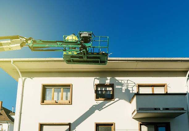 Modern hydraulic mobile construction platform with workers Modern hydraulic mobile construction platform elevated on the last floor of a house with construction worker preparing to to work subway platform stock pictures, royalty-free photos & images
