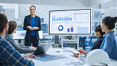istock Modern Industrial Factory Meeting: Confident Female Engineer Uses Interactive Whiteboard, Makes Report to a Group of Engineers, Managers Talks and Shows Statistics, Growth and Analysis Information 1282701229