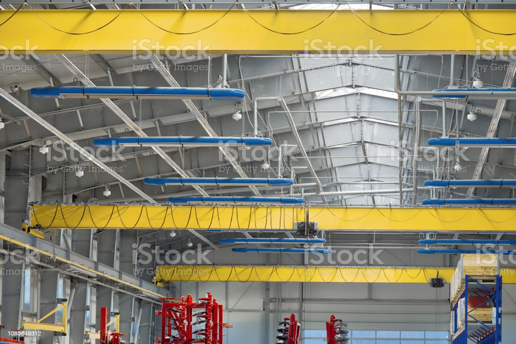 A modern industrial workshop, three overhead cranes under the ceiling stock photo