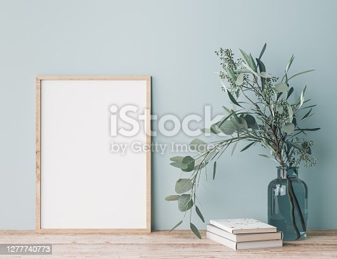 Modern interior close up with Eucalyptus in green vase, books and wooden frame. Wooden shelf and green wall