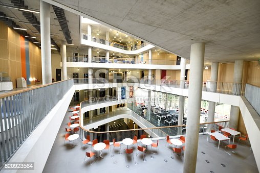elevated view of atrium of large modern concrete college building showing balcony, mezzanine and different storeys.
