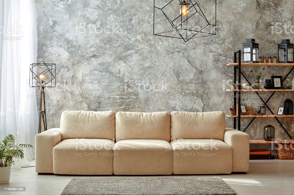 Picture of: Modern Interior Of Living Room With Gray Walls Beige Sofa Floor Lamp And Chandelier Light Carpet Shelf With Frames And Jars Flower In A Pot Stock Photo Download Image Now Istock