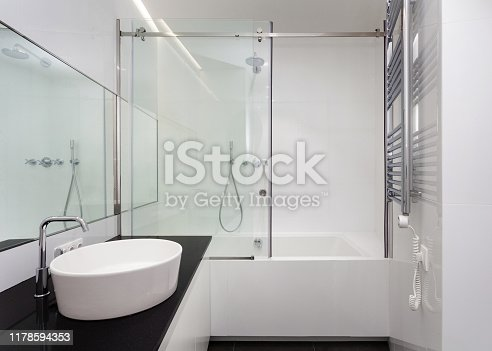 White bathroom with bathtub, basin, shower, large mirror and chrome silver heater or electric towel radiator on wall. Modern apartment with contemporary interior