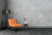istock Modern Interior With Orange Colored Leather Armchair, Sconce, Coffee Table And Gray Wall. 1296444787