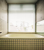 Modern Japanese bathroom with large window concrete walls