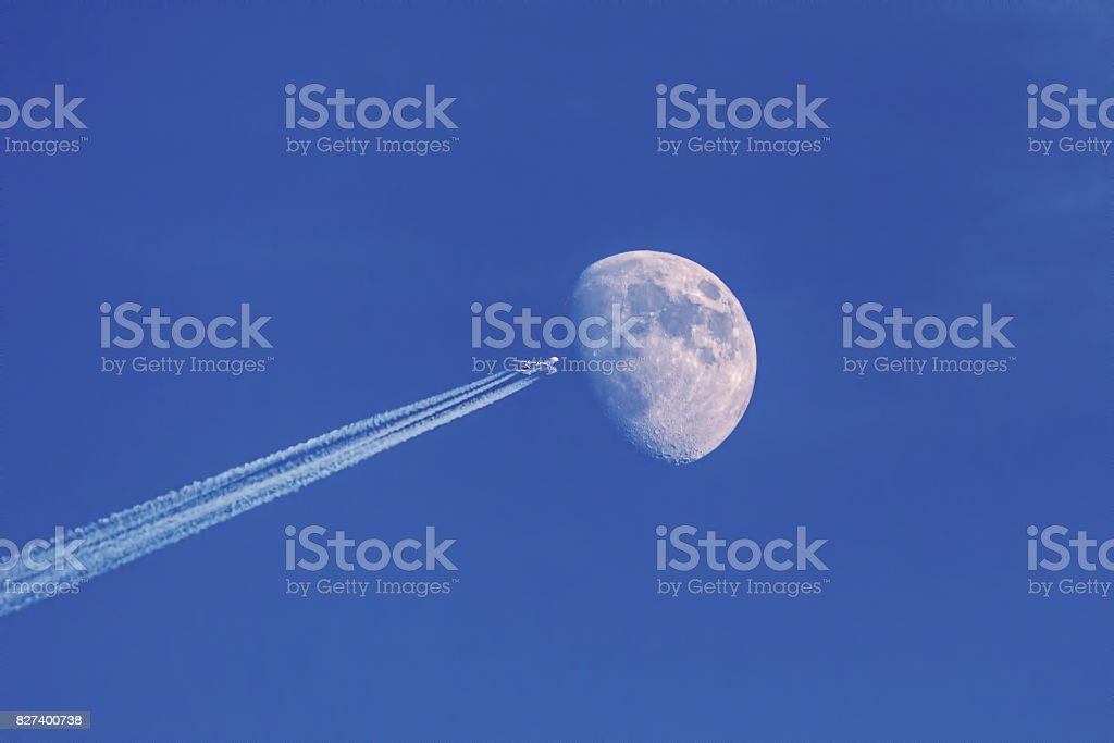 Modern jet plane with moon on blue sky stock photo