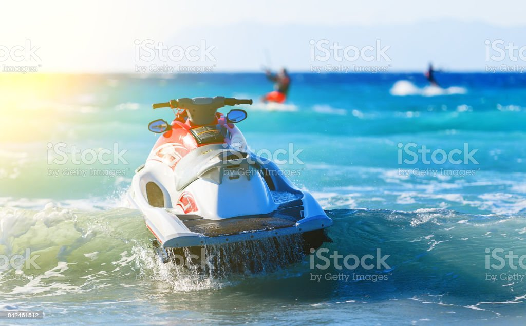 modern jet sways in the surf near shore on background of mountains in Greece stock photo