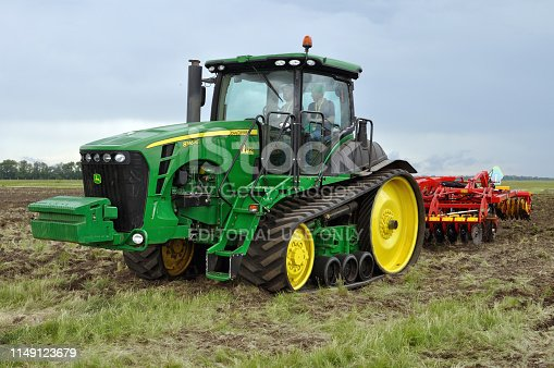 Cherkasy, Ukraine - May 18, 2018: Modern John Deere tractor model 8345RT ploughing an agricultural field with modern plough at the agricultural exhibition AGROSHOW