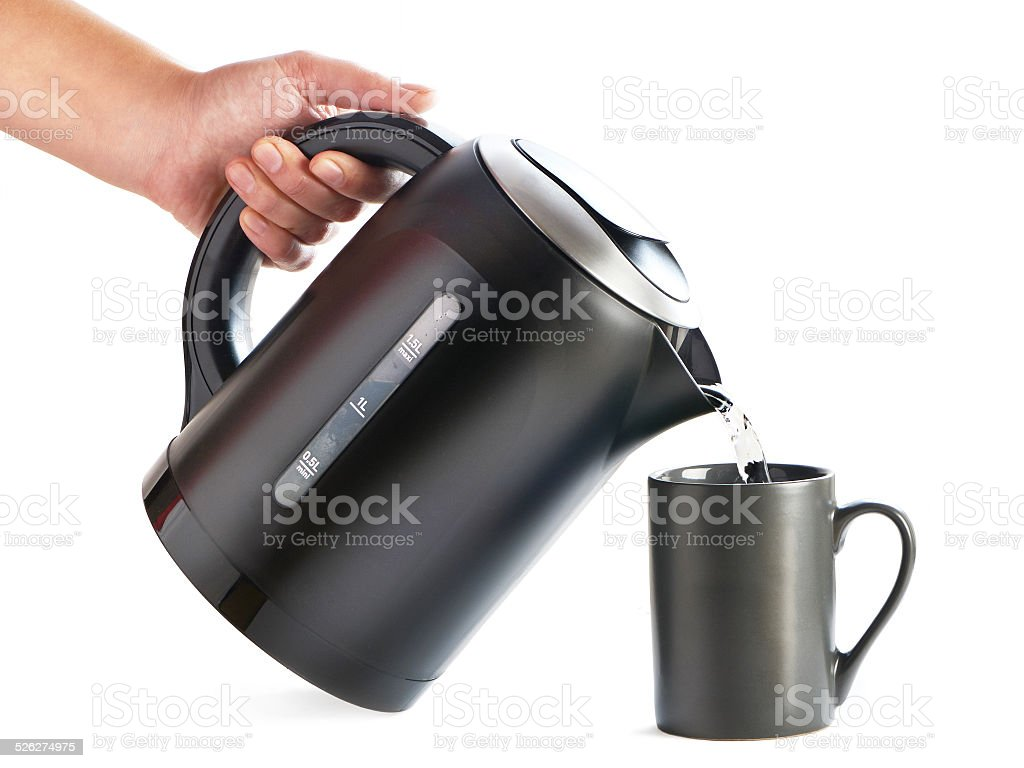 Modern kettle pouring water into cup isolated on white stock photo
