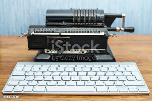 istock Modern keyboard and old adding machine 665410716