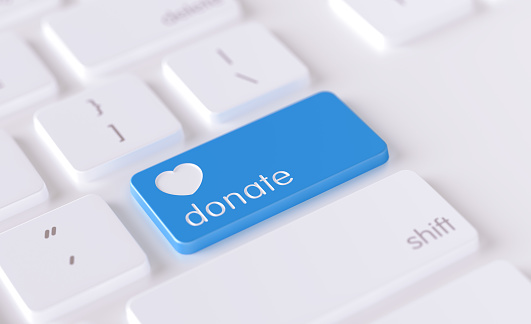 Donation  icon written on a blue button of a computer keyboard. Horizontal composition with selective focus and copy space. High angle view. Charity concept.