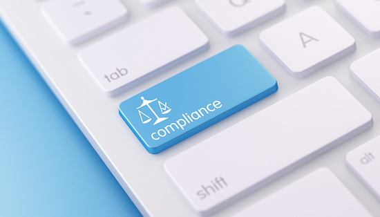 High quality 3d render of a modern keyboard with blue compliance button on a blue background and copy space. Blue compliance keyboard button has a text  and an icon on it. Compliance keyboard button is  in focus, Horizontal composition with copy space.