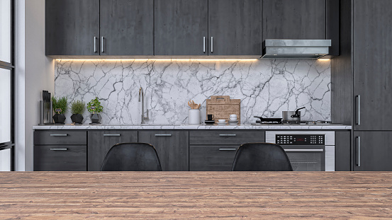 Empty modern kitchen with dark gray wooden kitchen cabinets, white and gray marble background and large hardwood dining table with copy space in the foreground. A window on a side and with focus on background. 3D rendered image.