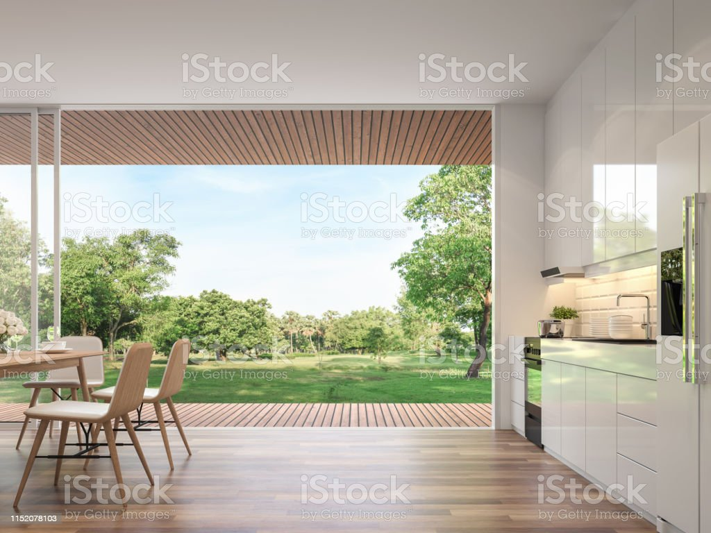 Modern kitchen and dining room with nature view 3d render Modern dining room 3d render.Rooms have wooden floors, decorated with wooden furniture and a glossy white kitchen counter with large open doors. Overlooking the terrace and large garden. Apartment Stock Photo