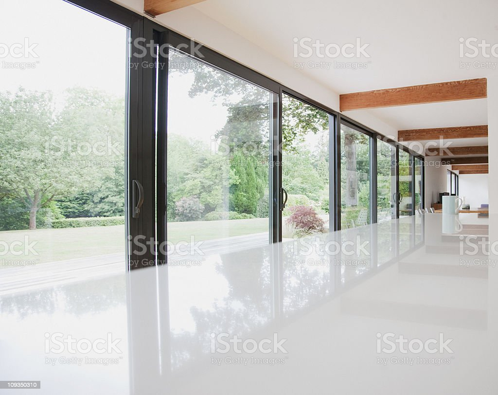 Modern kitchen and glass walls to backyard stock photo