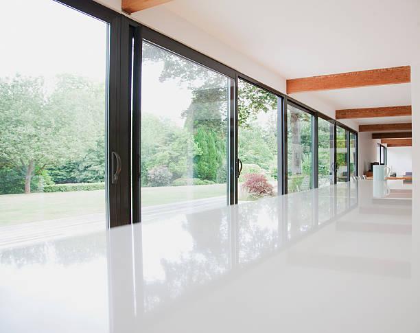 Modern kitchen and glass walls to backyard stock photo