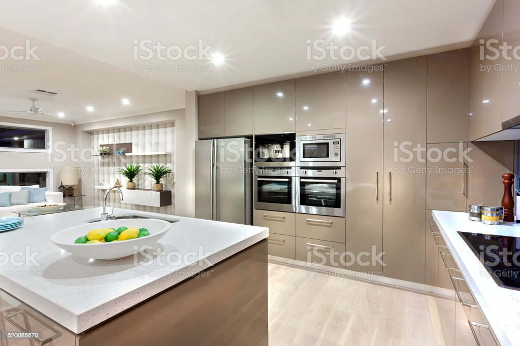 Modern kitchen area illuminated with lights at night stock photo