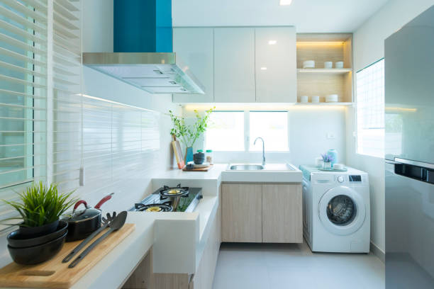 Modern kitchen counter with washing machine and cooking stove by the window. stock photo