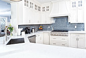 A contemporary home kitchen with stainless steel appliances and painted white cabinets.