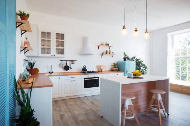 nowoczesne wnętrze kuchni z wyspą, umywalką, szafkami i dużym oknem w nowym luksusowym domu. - kuchnia zdjęcia i obrazy z banku zdjęć