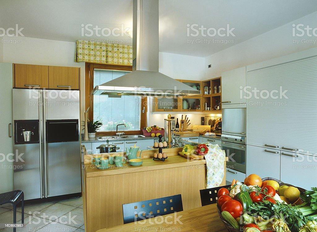 Modern kitchen: island, hood kitchen, wood and steel furnishings, vegetables stock photo