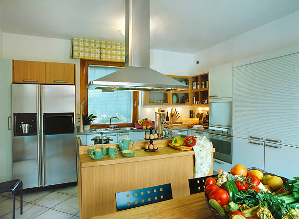 Modern kitchen: island, hood kitchen, wood and steel furnishings, vegetables stock photo