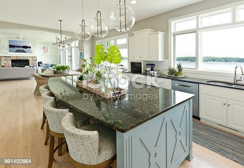+++NOTE TO INSPECTOR: Two photos artwork on the wall and on the table is taken by me, they are currently in the iStock collection, see property release.+++  A contemporary kitchen and living room with open concept design and bar counter in a modern home. A beautiful view to the lake in the exterior.