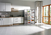 Wide angle shot of a domestic kitchen in morning light with open fridge