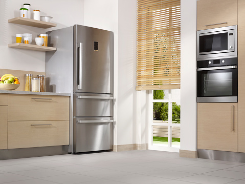 Wide angle shot of a domestic kitchen with stainless steel appliances