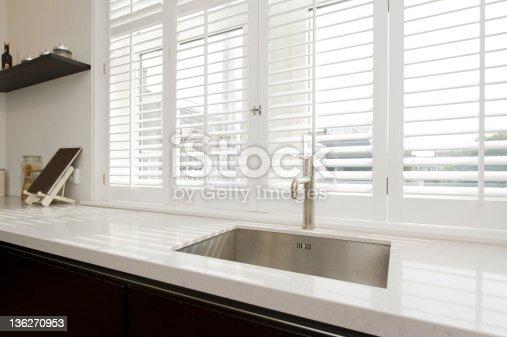 Modern kitchen dark brown with wooden blinds.