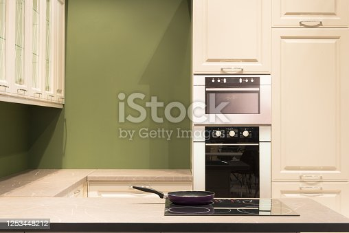 665910118 istock photo Modern kitchen room interior with furniture and pan on the stove for concept design - light home background 1253448212
