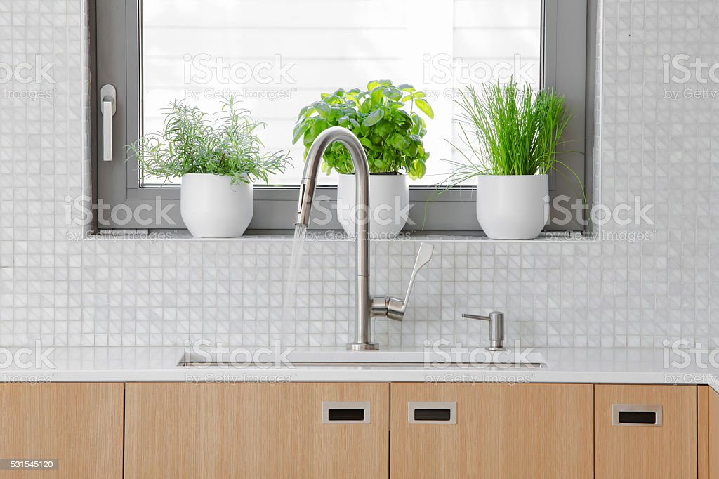 Modern kitchen Stainless steal faucet with water running into sink. stock photo