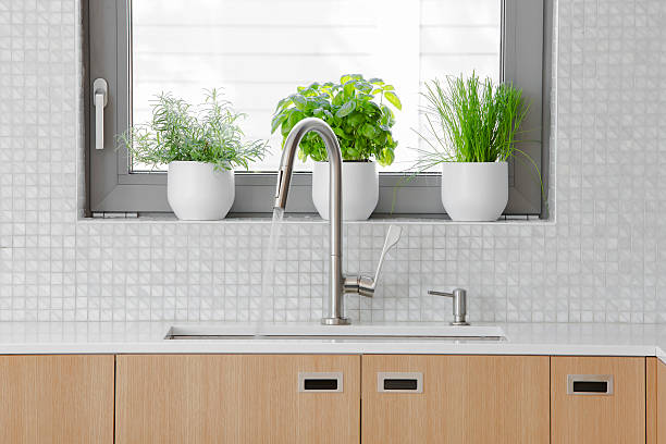 modern kitchen stainless steal faucet with water running into sink. - kitchen sink stock photos and pictures