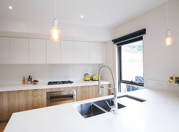 moderne küche mit licht aus hängelampen und eingelassenen spülbecken - laminatschränke stock-fotos und bilder