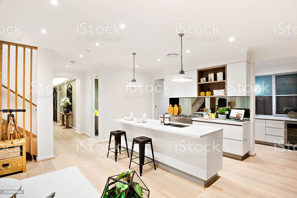 Modern kitchen with white walls illuminated by hanging lamps stock photo