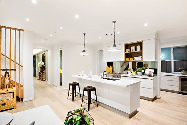 modern kitchen with white walls illuminated by hanging lamps - bodenleuchten stock-fotos und bilder